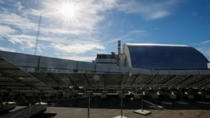 Sun shines on Solar panels in front of the the damaged fourth reactor of the Chernobyl nuclear plant, at solar power plant in Chernobyl, Ukraine on 5 October 2018.