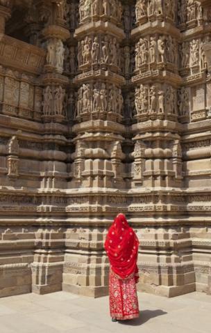 Uma mulher de burca admira esculturas eróticas em um templo