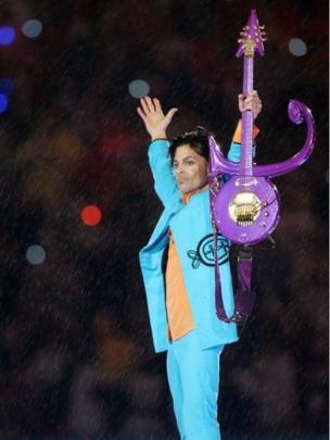 名前として使ったシンボルマークに模したギターを手にするプリンス。2007年2月のスーパーボウル、ハーフタイム・ショーで。