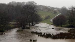A field near Nettleton, Wiltshire, is flooded due to the high amounts of rain as Storm Angus continues to sweep across the UK.