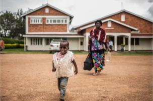 """Criscent sai do hospital com seus óculos novos. """"Antes da cirurgia, ele dependia de sua avó ou de outro parente para fazer qualquer coisa. Mas agora é uma criança independente e segura"""", diz Joseph Magyezi, funcionário do hospital."""