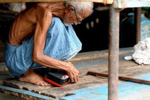 رجل مسن يصلح راديو