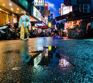 A puddle reflects the neon shop signs and passersby walk past