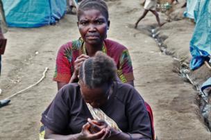 La vie continue dans le camp juste à côté une femme fait des tresses à sa voisine.