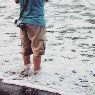 Hombre mojándose los pies en la playa
