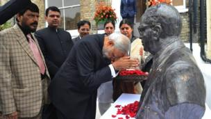 Indian Prime Minista Narendra Modi bowin by a funky-ass bust of Dr Ambedkar