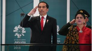 Indonesian President Joko Widodo salutes next his wife Iriana Widodo during the opening ceremony of the 2018 Asian Games
