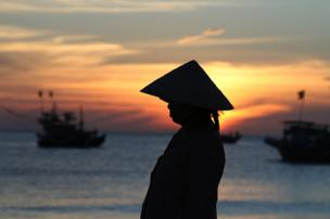 The silhouette of a fisherman in a traditional hat