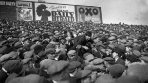 Fans pass a young boy over their heads to the front so that he can see the game better, 1 March 1930