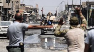 عراقيون فارون من القتال الدائر في مدينة الموصل القديمة يمتطون ظهر عربة مدرعة للقوات العراقية في الحي الصناعي للمدينة