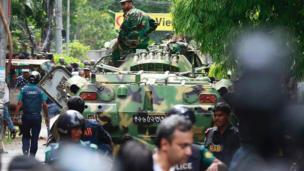 Bangladeshi soldiers and security personnel sit on top of armoured vehicles as they cordon off an area near a restaurant popular with foreigners after heavily armed militants took dozens of hostages, in a diplomatic zone of the Bangladeshi capital Dhaka, Bangladesh, Saturday, 2 July 2016.