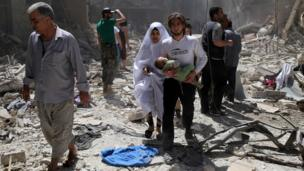 A Syrian family walks amid the rubble of destroyed buildings following a reported airstrike on April 28, 2016 in the Bustan al-Qasr rebel-held district of the northern Syrian city of Aleppo.