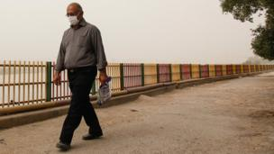 مردی در حال راه رفتن در هوای آلوده اهواز