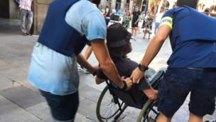 Police help a man in a wheelchair to leave the area around the Ramblas