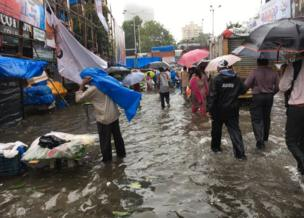 People trying to navigate the streets flooded with rain, umbrellas at hand.