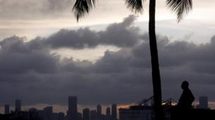 A silhouette of a man and a palm tree with Miami skyline and clouds behind him