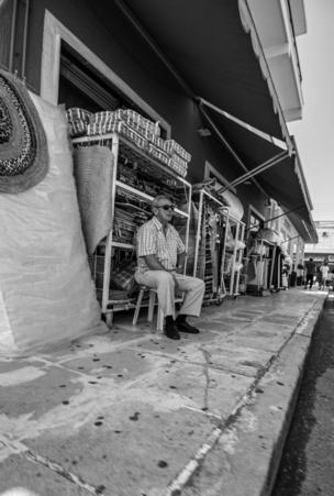 A man sits at the side of a street watching the world go by