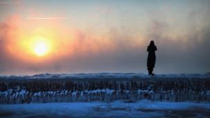 Hombre parado sobre un bloque de hielo frente al Sol.