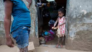 A girl helps her mother remove mud from her house after Hurricane Matthew flooded their home in Les Cayes, Haiti