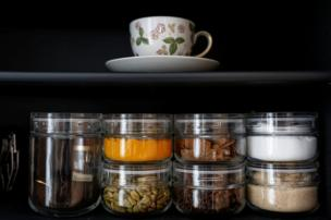 Glasses and spices sit on a shelf in the apartment of minimalist Saeko Kushibiki in Fujisawa