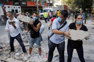 Across Mexico City, group of rescue workers and volunteers use shovel and dia bare hand carry blocks from di broken pieces of buildings wey di earthquake fall.