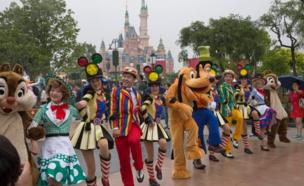 A line of Disney staff dressed in character and other costumes, dance during a parade at the park, with the centrepiece castle in the background, 15 June 2016.