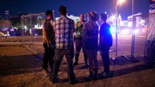 four people in festival clothes talking to a man in high vis