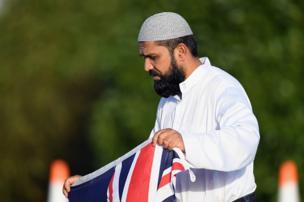 یکی از عزاداران حادثه کرایستچرچ با پرچم نیوزیلند در قبرستان محل دفن کشتهشدگان