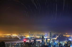 صورة التقطت من فوق قمة فيكتوريا، أعلى جبل في جزيرة هونج كونج، وتظهر المدينة في حالة صخب على نقيض سماء هادئة تسطع فيها النجوم.