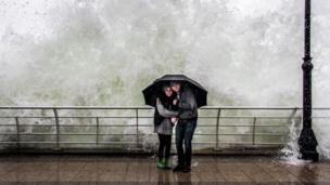 Couple in front of large wave