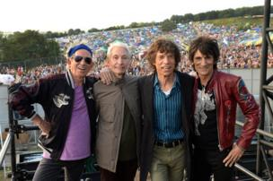 The Rolling Stones pose for a portrait in front of crowds