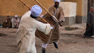 رجلان يتقاتلان بالعصي