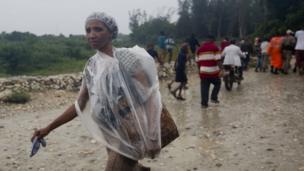 Mwanamke ajifunika kwa kutumia karatasi ya plastiki kabla ya kuwasili kwa Kimbunga Mathew, Tambare Haiti.
