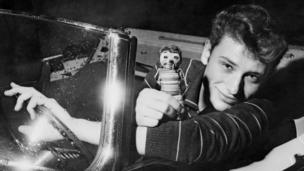 This file photo taken in the 1960s shows French singer Johnny Hallyday in a car
