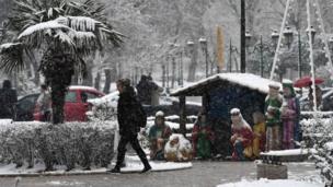 ग्रीस के थैसोलिनिकी में क्रिस्मस की एक दुकान के पास बर्फ़बारी के बीच हाथ अपने कोट की जेब में डाले गुज़रती महिला.