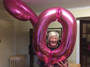 Mujer sonríe con globos de su 90 cumpleaños.