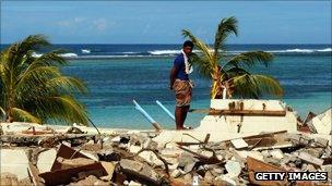 Man looks at damage caused by tsunami
