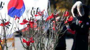 Participants tie red ribbons on Rose of Sharon trees in honour of 516 Canadian troops who lost their lives in the Korean War (1950-1953) ahead of Remembrance Day at the Rose of Sharon Garden in James Gardens in Toronto, Ontario, Canada