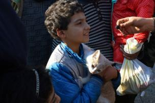 A boy, who was evacuated with others from a rebel-held area of Aleppo, is interviewed upon his arrival with his cat at insurgent-held al-Rashideen still holding his cat