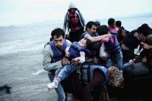 An Afghan refugee carries his child as he arrives on a beach on the Greek island of Kos, after crossing a part of the Aegean Sea between Turkey and Greece