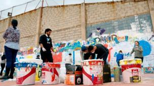 Youths paint a wall in the local sports centre during a visit to Fanzara near Castellon de la Plana