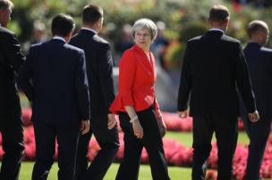Theresa May departs from a meeting in Salzburg