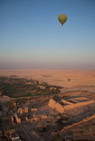 A hot air balloon flies over a temple