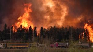 Trucks near the flames at Fort McMurray, Alberta