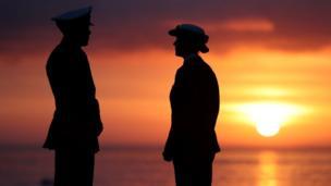 Crew members stand in sunlight