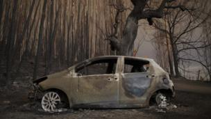 A burned car stands next to a forest after a wildfire took dozens of lives on June 18, 2017 near Castanheira de Pera, in Leiria district, Portugal, 18 June 2017.
