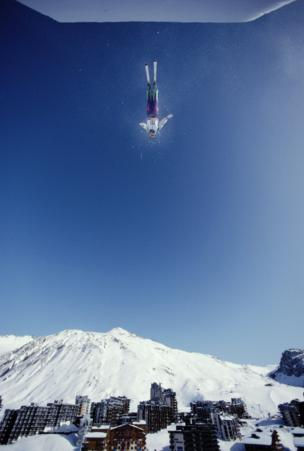 A Freestyle skiing competitor is suspended in the sky.