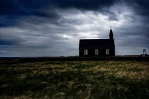A church on top of a hill with the backdrop of a stormy sky