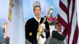 Rev Yeon Ah Lee Moon of the Sanctuary Church holds a gold AR-15