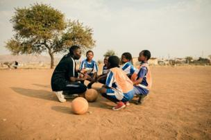 أطفال مع مدربهم في ملعب ترابي
